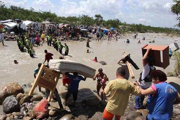 People carrying their household belongings across the Táchira River that separates Venezuela from the city of Cúcuta, Colombia, last month. PHOTO: ELIECER MANTILLA/ASSOCIATED PRESS